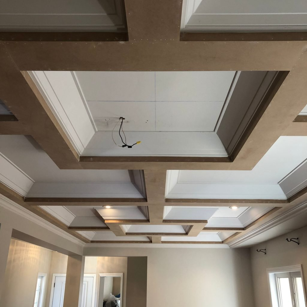 living room with coffered ceiling in custom home