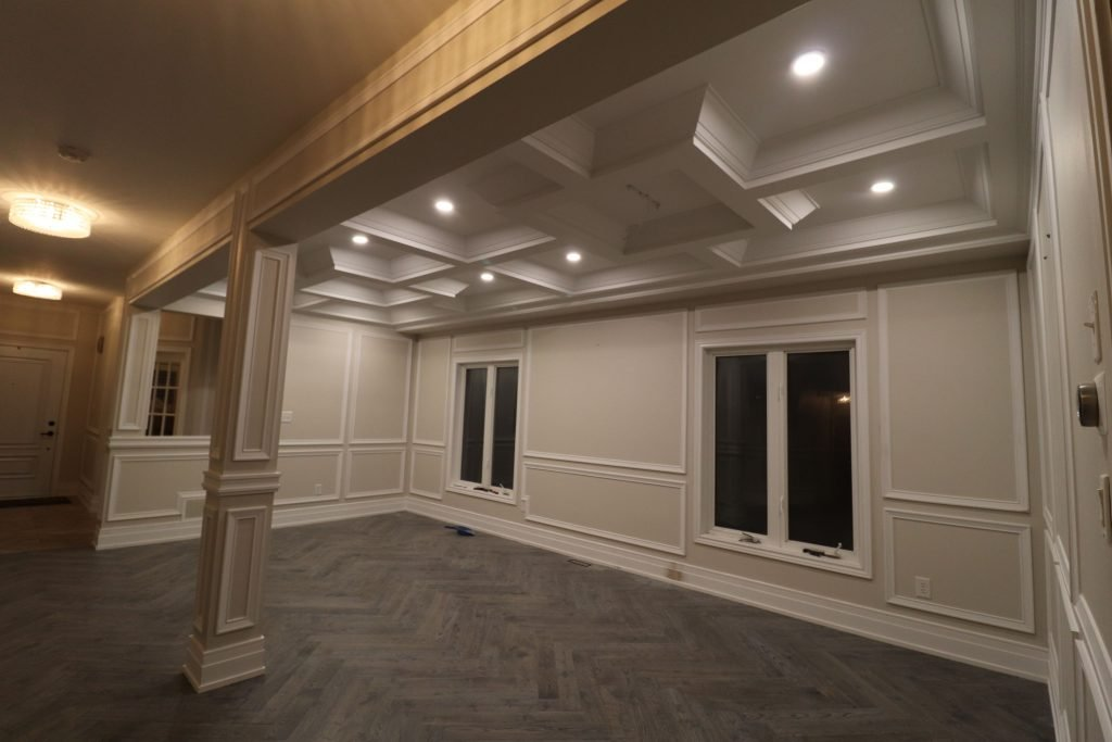 custom basement family room with baseboard trim and waffle ceiling