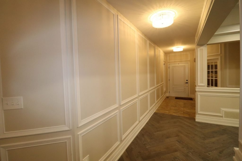 classic hallway with baseboard trim and wainscoting wall decor