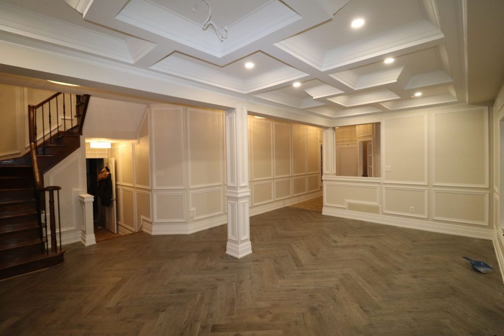 basement living room with column decor and waffle ceiling