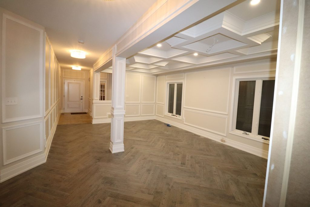 custom basement with Wainscoting wall decor and waffle ceiling