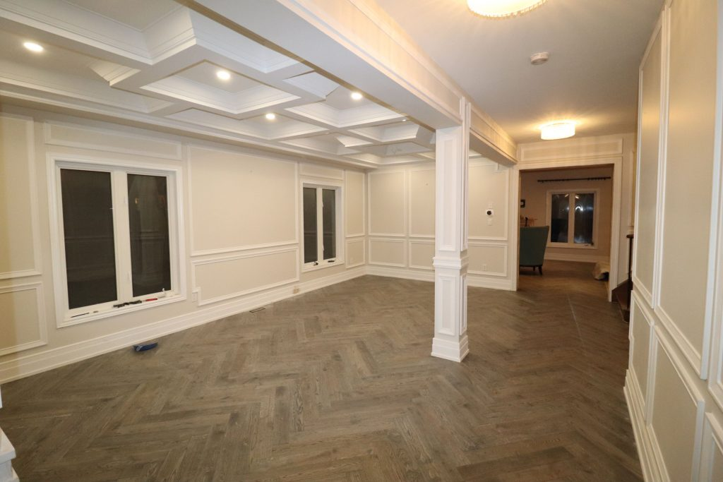 custom basement living room with waffle ceiling and wainscoting wall décor