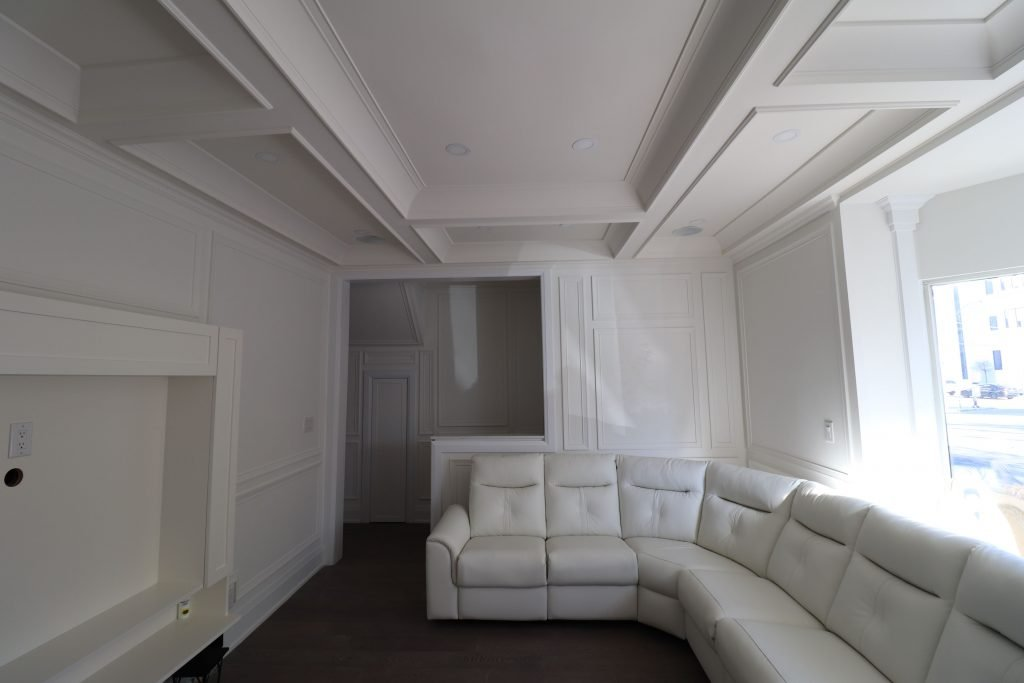 L shape white sofa and waffle ceiling in custom living room
