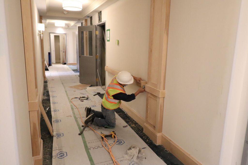 trim team installing wooden railings and baseboard trim